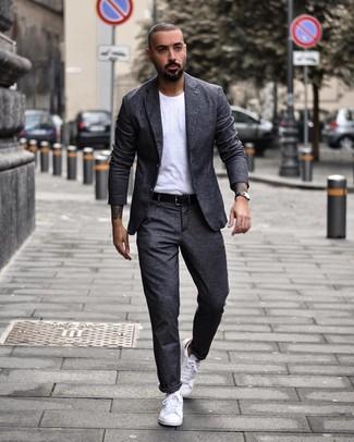 Cómo combinar: traje de lana en gris oscuro, camiseta con cuello circular blanca, tenis blancos, correa de cuero negra