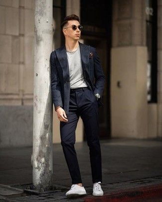 Outfits hombres en clima cálido: Si buscas un estilo adecuado y a la moda, elige un traje azul marino y una camiseta con cuello circular gris. ¿Quieres elegir un zapato informal? Opta por un par de tenis de cuero blancos para el día.