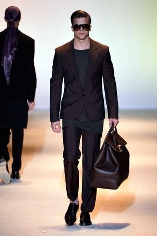 Cómo combinar: traje negro, camiseta de manga larga en gris oscuro, zapatos oxford de cuero negros, bolso baúl de cuero en marrón oscuro