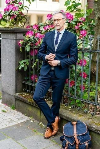 Cómo combinar una mochila de lona azul marino: Para crear una apariencia para un almuerzo con amigos en el fin de semana empareja un traje azul marino junto a una mochila de lona azul marino. Con el calzado, sé más clásico y elige un par de zapatos derby de cuero en tabaco.