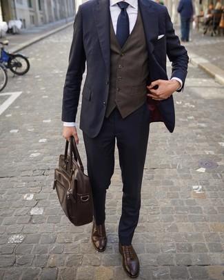 Outfits hombres: Considera ponerse un traje azul marino y un chaleco de vestir en marrón oscuro para una apariencia clásica y elegante. Si no quieres vestir totalmente formal, opta por un par de zapatos brogue de cuero en marrón oscuro.