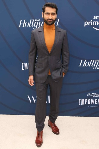 Cómo combinar: traje de rayas verticales en marrón oscuro, jersey de cuello alto naranja, botas formales de cuero marrónes