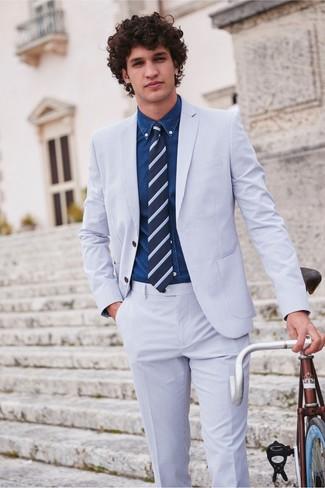 Cómo combinar: traje de seersucker celeste, camisa vaquera azul marino, corbata de rayas horizontales azul marino