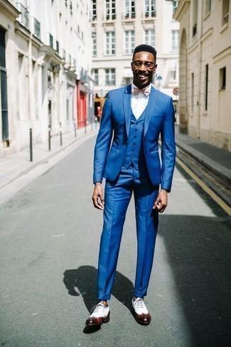 Cómo combinar un corbatín: Ponte un traje de tres piezas azul y un corbatín para lidiar sin esfuerzo con lo que sea que te traiga el día. Con el calzado, sé más clásico y complementa tu atuendo con zapatos brogue de cuero blancos.