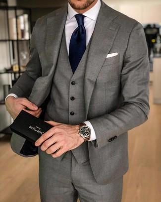 Cómo combinar una corbata de seda azul marino: Utiliza un traje de tres piezas gris y una corbata de seda azul marino para un perfil clásico y refinado.