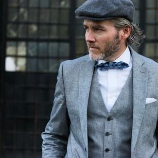 Cómo combinar: traje de tres piezas de rayas verticales gris, camisa de vestir blanca, gorra inglesa en gris oscuro, corbatín de tartán azul