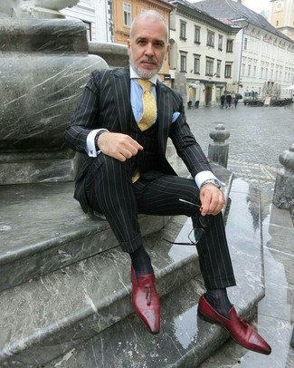 Cómo combinar: traje de tres piezas de rayas verticales negro, camisa de vestir celeste, mocasín con borlas de cuero rojo, corbata a lunares amarilla