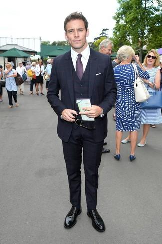 Cómo combinar: traje de tres piezas a cuadros azul marino, camisa de vestir blanca, zapatos derby de cuero negros, corbata estampada morado oscuro