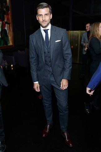 Cómo combinar: traje de tres piezas de lana en gris oscuro, camisa de vestir blanca, zapatos oxford de cuero en marrón oscuro, corbata de punto azul marino