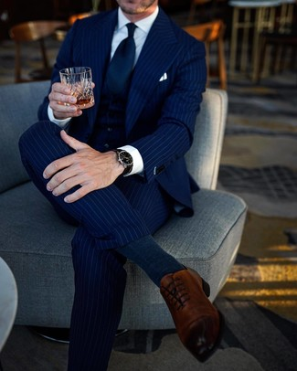 Outfits hombres: Considera ponerse un traje de tres piezas de rayas verticales azul marino y una camisa de vestir blanca para un perfil clásico y refinado. Zapatos oxford de cuero marrónes son una opción inmejorable para complementar tu atuendo.