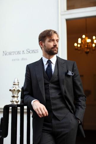Cómo combinar: traje de tres piezas de rayas verticales negro, camisa de vestir blanca, corbata azul marino, pañuelo de bolsillo a lunares en negro y blanco