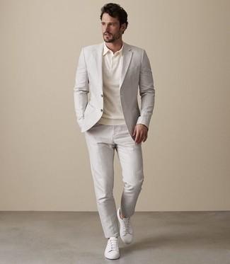 Cómo combinar: traje en beige, camisa polo en beige, tenis de cuero blancos