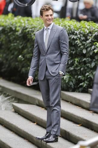 Look de Jamie Dornan: Traje Gris, Camisa de Vestir Blanca, Zapatos Derby de Cuero Negros, Corbata Gris