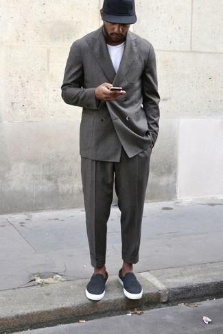 Outfits hombres: Si buscas un estilo adecuado y a la moda, utiliza un traje gris y una camiseta con cuello circular blanca. ¿Quieres elegir un zapato informal? Opta por un par de zapatillas slip-on de lona en gris oscuro para el día.