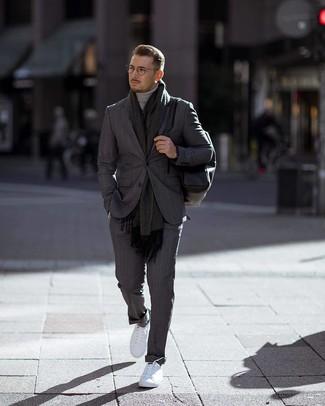 Cómo combinar: traje de rayas verticales en gris oscuro, jersey de cuello alto gris, tenis blancos, mochila de cuero negra