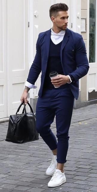 Cómo combinar una bolsa tote de cuero negra: Empareja un traje azul marino con una bolsa tote de cuero negra para un almuerzo en domingo con amigos. Tenis de lona blancos son una opción atractiva para completar este atuendo.