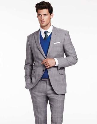 Emparejar un jersey de pico azul junto a un traje de tartán gris es una opción atractiva para una apariencia clásica y refinada.