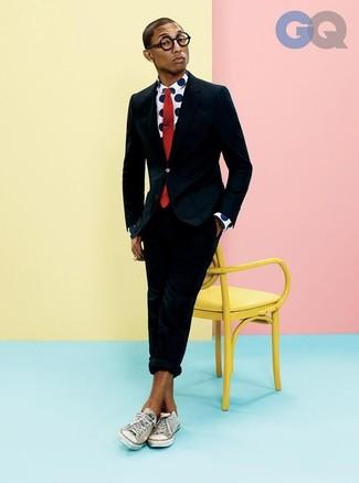 Cómo combinar: traje negro, camisa de manga larga a lunares en blanco y azul marino, tenis de lona blancos, corbata roja