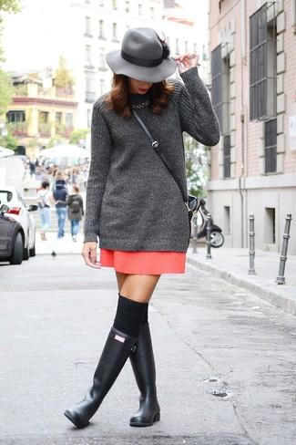 Cómo combinar: túnica de punto en gris oscuro, minifalda roja, botas de lluvia negras, calcetines hasta la rodilla negros