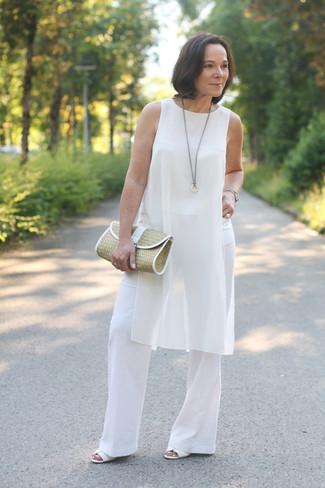 Cómo combinar: túnica de seda blanca, pantalones anchos blancos, sandalias de tacón de cuero blancas, cartera sobre de paja marrón claro
