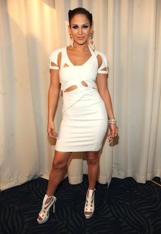 Look de Jennifer Lopez: Vestido Ajustado con Recorte Blanco, Sandalias de Tacón de Cuero Blancas, Pulsera Plateada, Pendientes Plateados