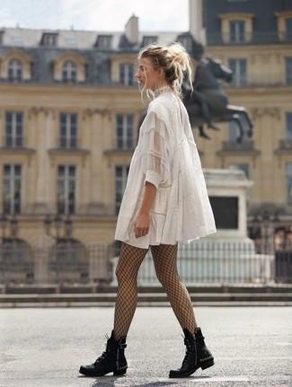 Cómo combinar: vestido amplio de encaje blanco, botas planas con cordones de cuero con tachuelas negras, medias de red negras
