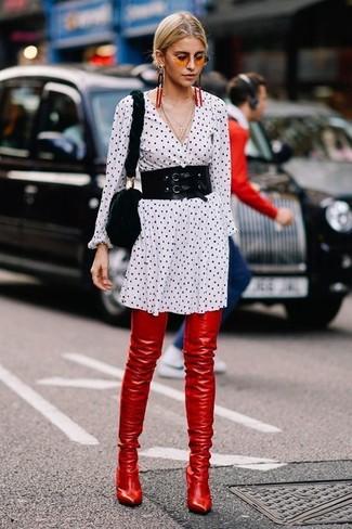 Cómo combinar: vestido camisa a lunares en blanco y negro, botas sobre la rodilla de cuero rojas, bolso bandolera de pelo negro, cinturón negro