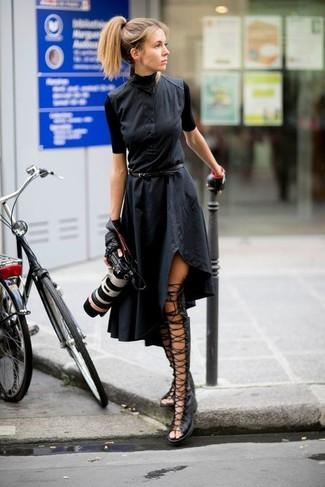 Cómo combinar: vestido camisa negra, sandalias romanas altas de cuero negras, guantes de cuero negros