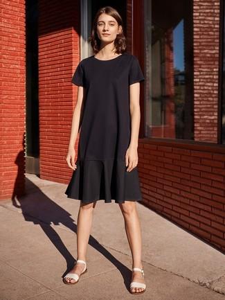 Cómo combinar unas sandalias planas de cuero blancas estilo relajado: Usa un vestido casual con volante negro para un look agradable de fin de semana. Este atuendo se complementa perfectamente con sandalias planas de cuero blancas.