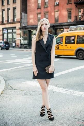 Cómo combinar: vestido de esmoquin negro, zapatos de tacón de ante negros, cartera sobre dorada, pulsera dorada