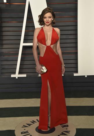 Look de Miranda Kerr: Vestido de Noche con Recorte Rojo, Sandalias de Tacón de Cuero Doradas, Cartera Sobre Dorada, Pulsera Dorada