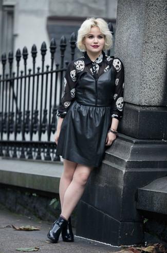 Cómo combinar: vestido de tirantes de cuero negro, camisa de vestir de gasa estampada en negro y blanco, botines de cuero negros