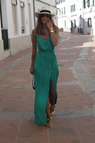 Cómo combinar: vestido largo verde, sandalias de dedo de cuero doradas, cartera sobre de cuero en negro y blanco, sombrero de paja en beige