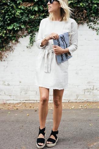 Cómo combinar: vestido recto blanco, sandalias con cuña de ante negras, cartera sobre de lona de rayas verticales en blanco y azul, gafas de sol negras