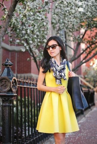 Cómo combinar: vestido skater amarillo, bolsa tote de cuero azul marino, bufanda estampada en blanco y azul marino, gafas de sol en marrón oscuro