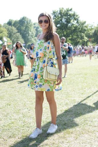 Cómo combinar: vestido skater con print de flores en multicolor, tenis de lona blancos, bolso bandolera de cuero amarillo, gafas de sol en marrón y dorado