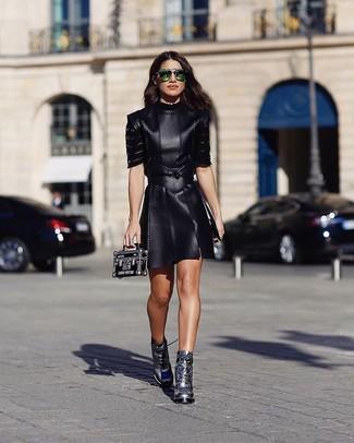 Cómo combinar: vestido skater de cuero negro, botines con cordones de cuero plateados, cartera sobre de cuero negra, gafas de sol verdes