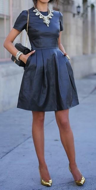 Para seguir las tendencias usa un vestido skater de cuero negro. ¿Te sientes ingenioso? Dale el toque final a tu atuendo con zapatos de tacón de cuero dorados.