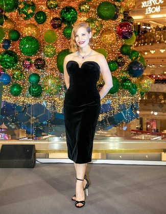 Moda para mujeres de 40 años: Haz de un vestido tubo de terciopelo negro tu atuendo para un conjunto de oficina con estilo. Sandalias de tacón de satén negras son una opción práctica para completar este atuendo.