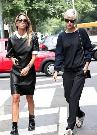 Cómo combinar: vestido tubo de cuero negro, camisa de manga corta blanca, botines de cuero con recorte negros, cartera sobre de cuero con tachuelas negra